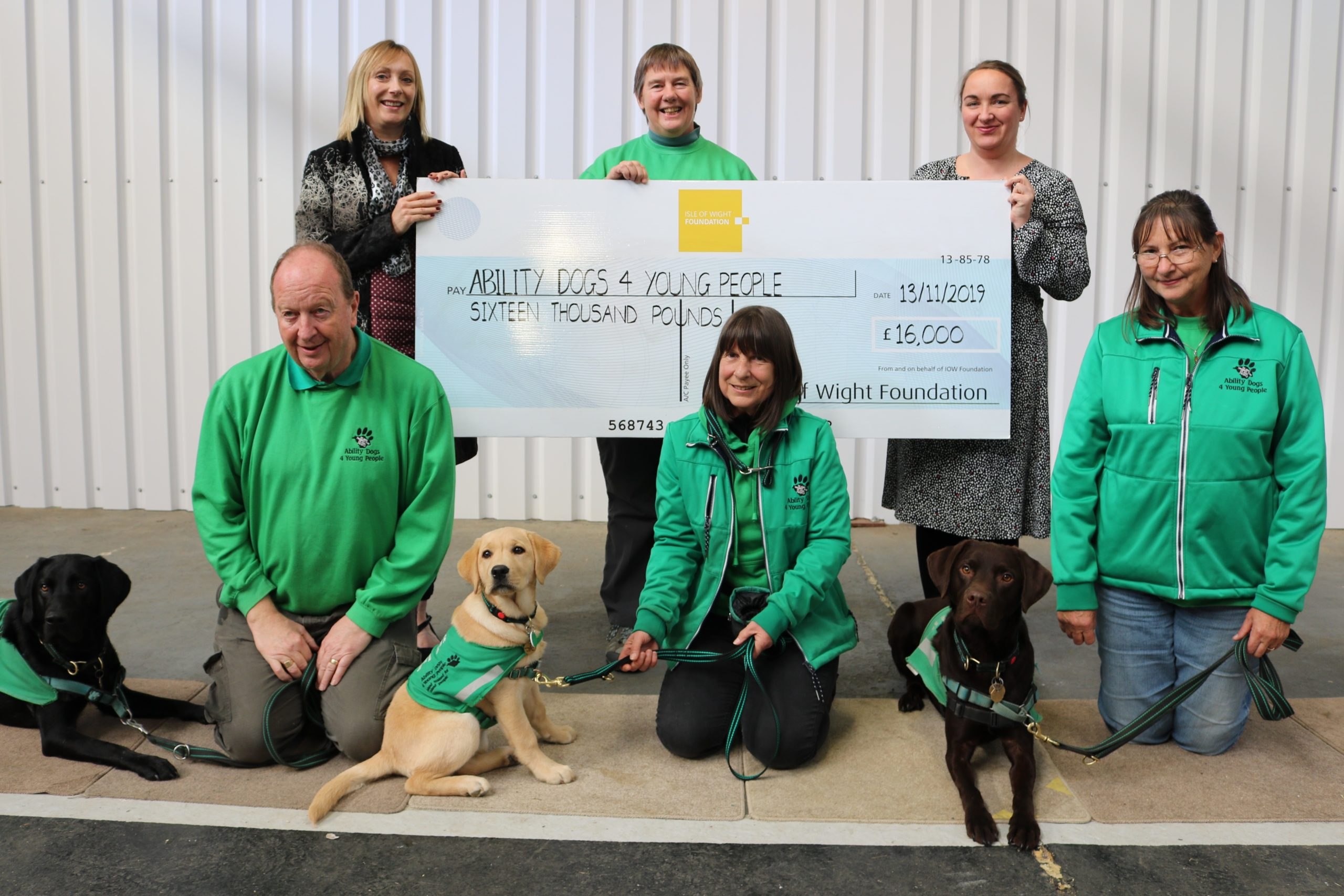 photo showing adults from Island Roads and Ability Dogs for Young People charity with dogs and a large cheque