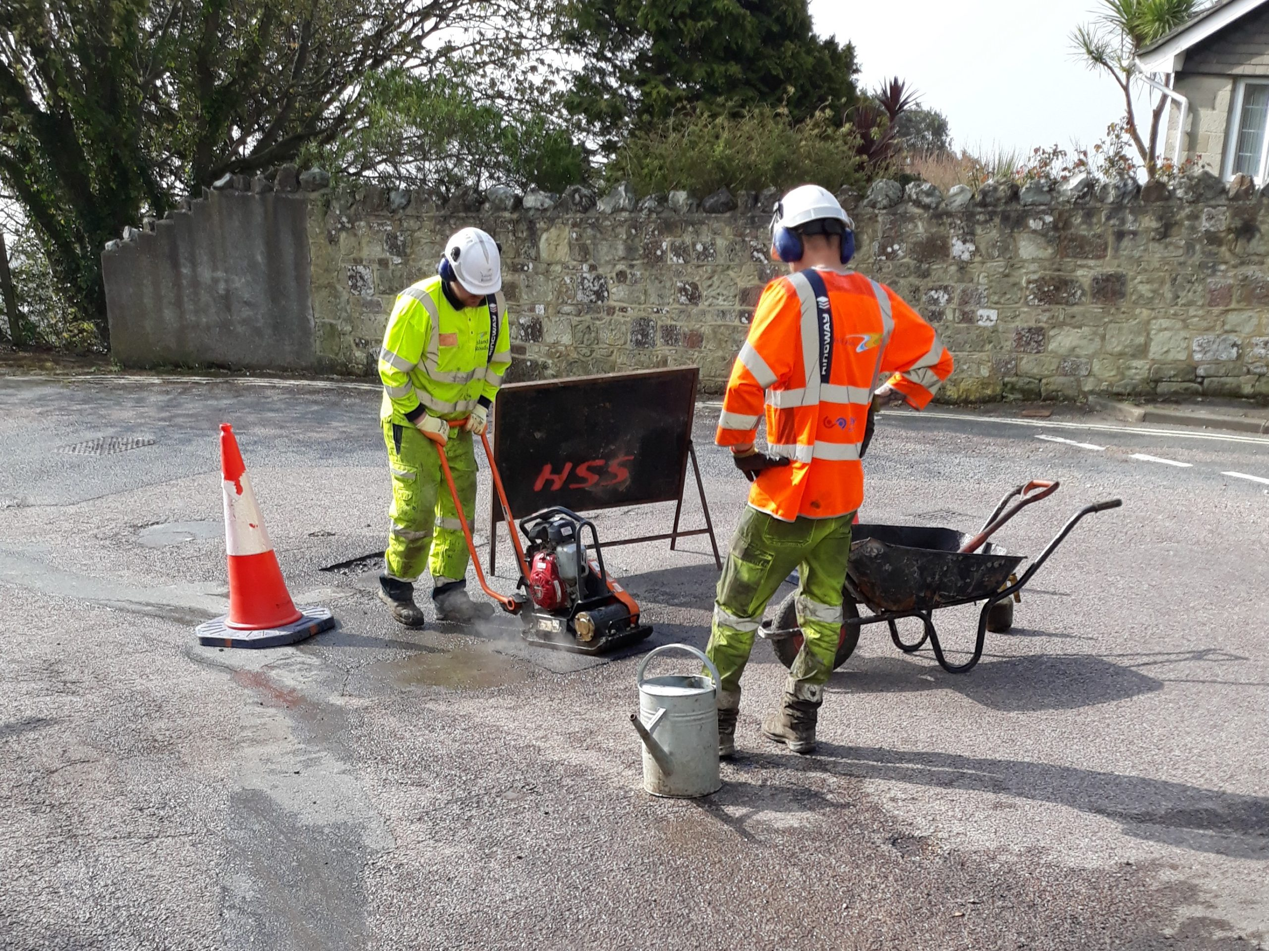 Photo showing two Island Roads operatives repairing a pot hole in the road
