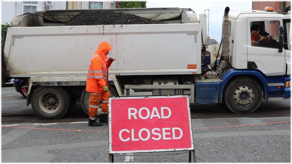 Photo showing road closed sign and vehicle and operative working in the background