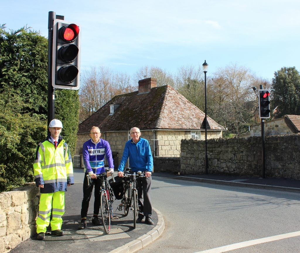Photo showing cyclists and Island Roads staff member at traffic signals in Shalfleet