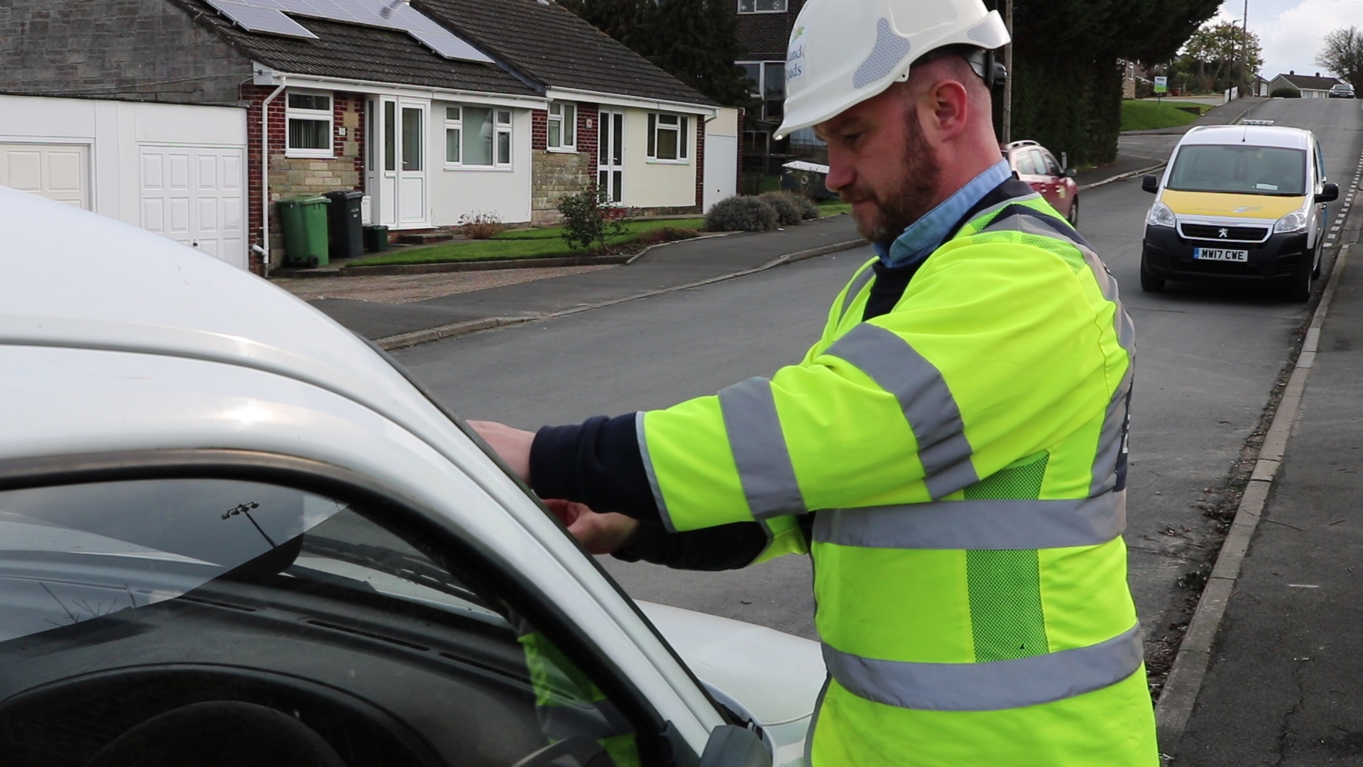 Photo showing Island Roads District Steward affixing a notice to an abandoned vehicle left in the street
