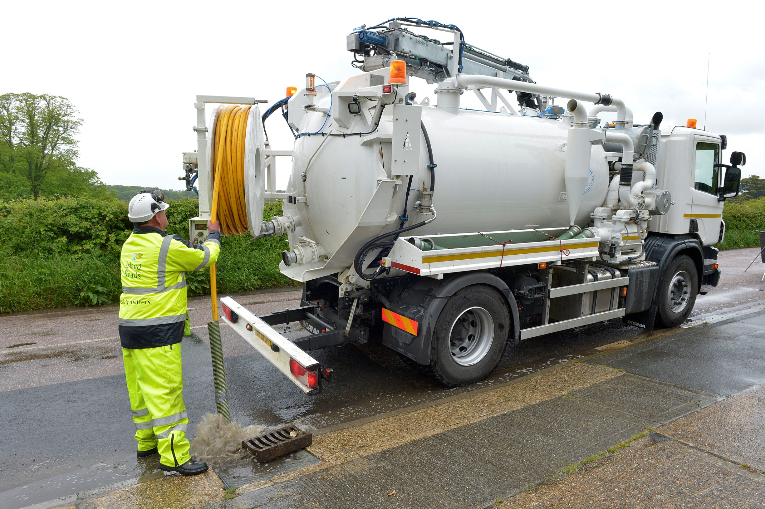 Photo showing Island Roads employee using a gully cleansing vehicle to clear out a drain.