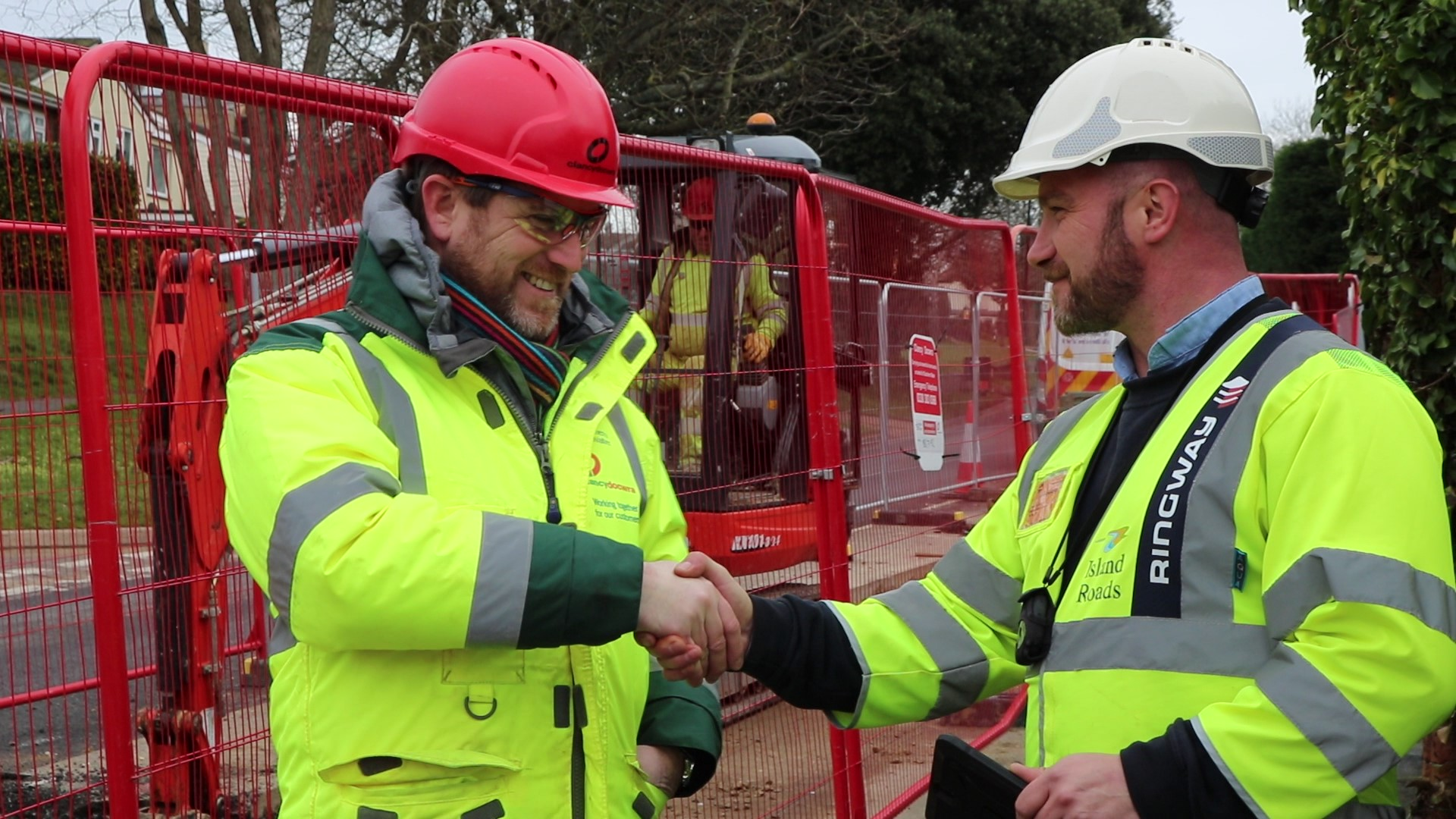 Photo showing Southern Water and Island Roads staff members shaking hands in front of work site