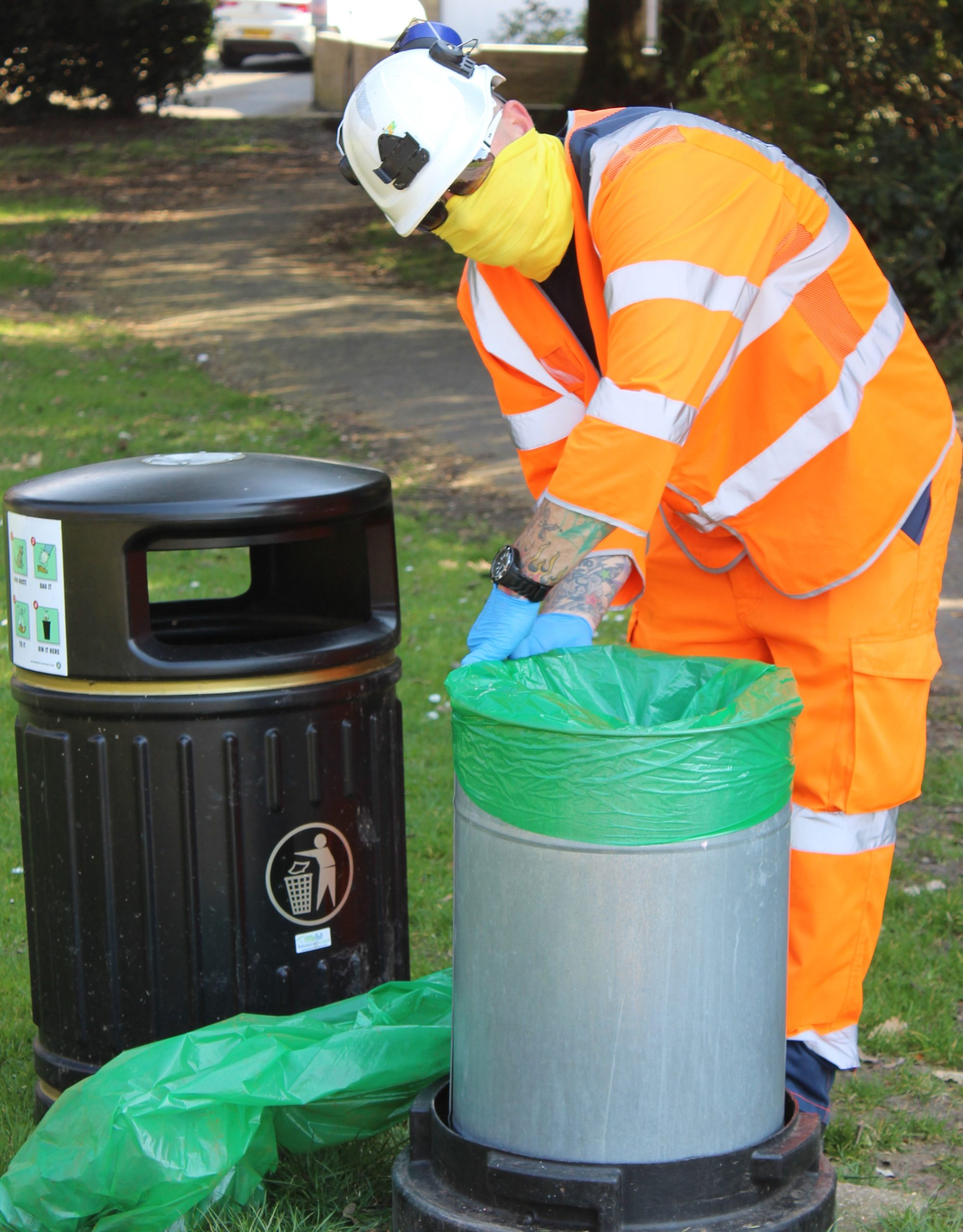 Photo showing Island Roads staff member emptying litter bins dressed in protective clothing