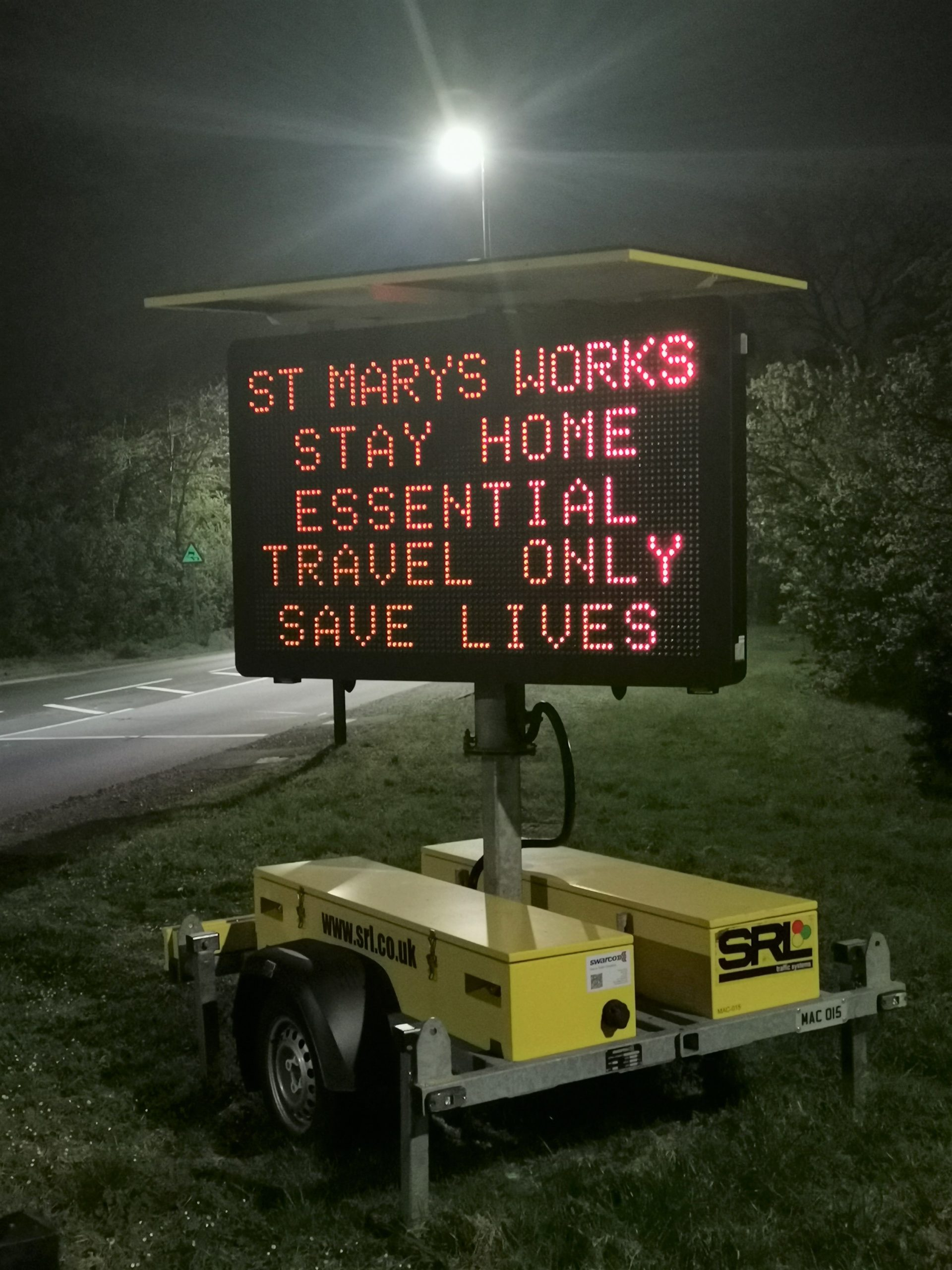 Photo showing essential health messaging on VMS signs on the roadside near St Mary's advising people to stay home, essential travel only, save lives. Photo taken at night.