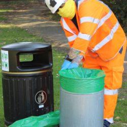 Photo showing an Island Roads operative emptying a litter bin