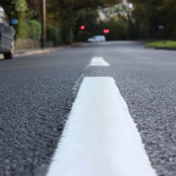 Image of a white line in the middle of a newly resurfaced road