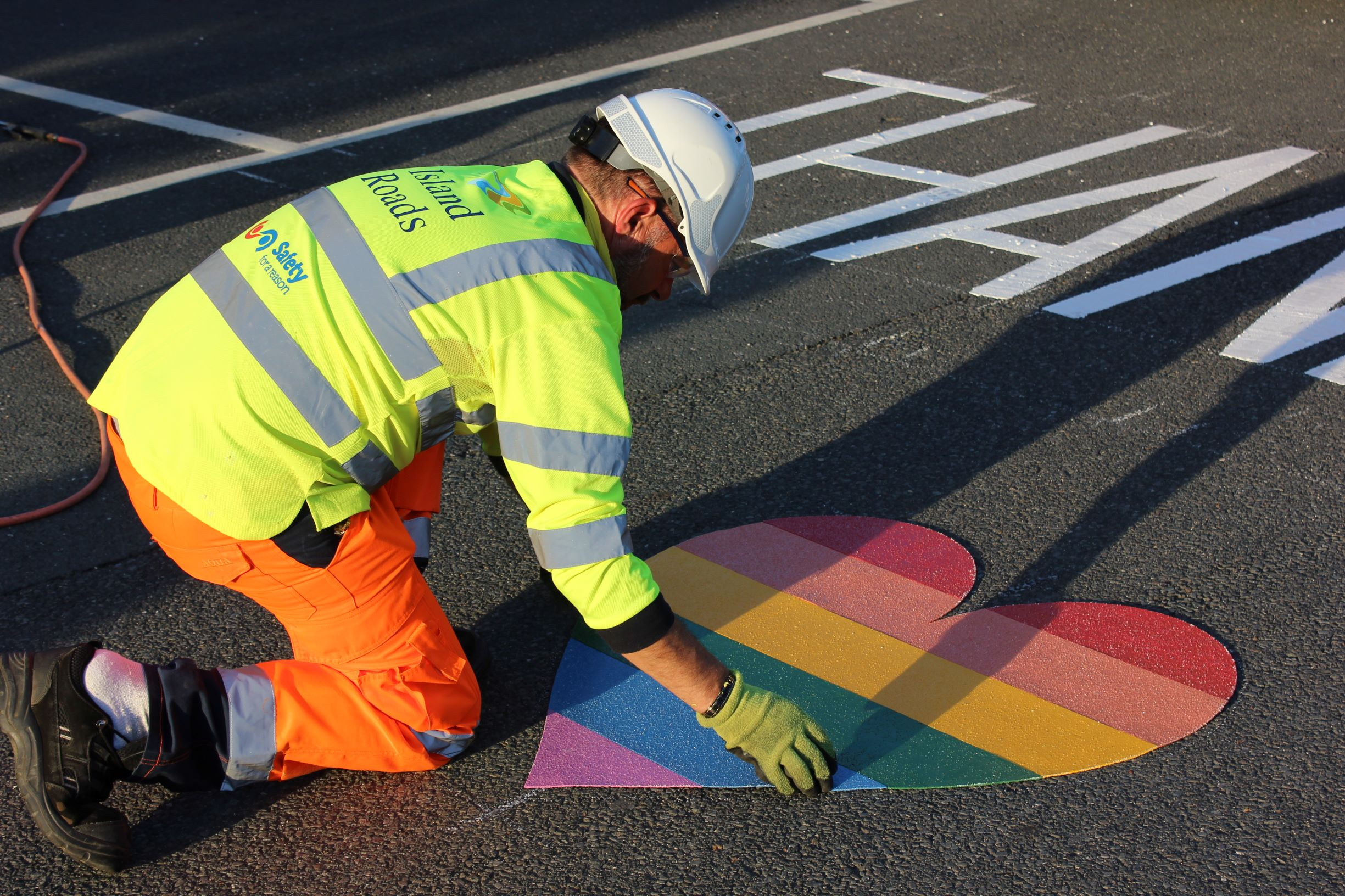 Photo showing Island Roads crew member putting painted heart in place on the Hospice grounds as a thank you to staff