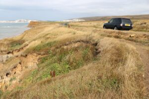 photo showing the proximity of coastal erosion to the highway at Brook, cars on road passing Chine