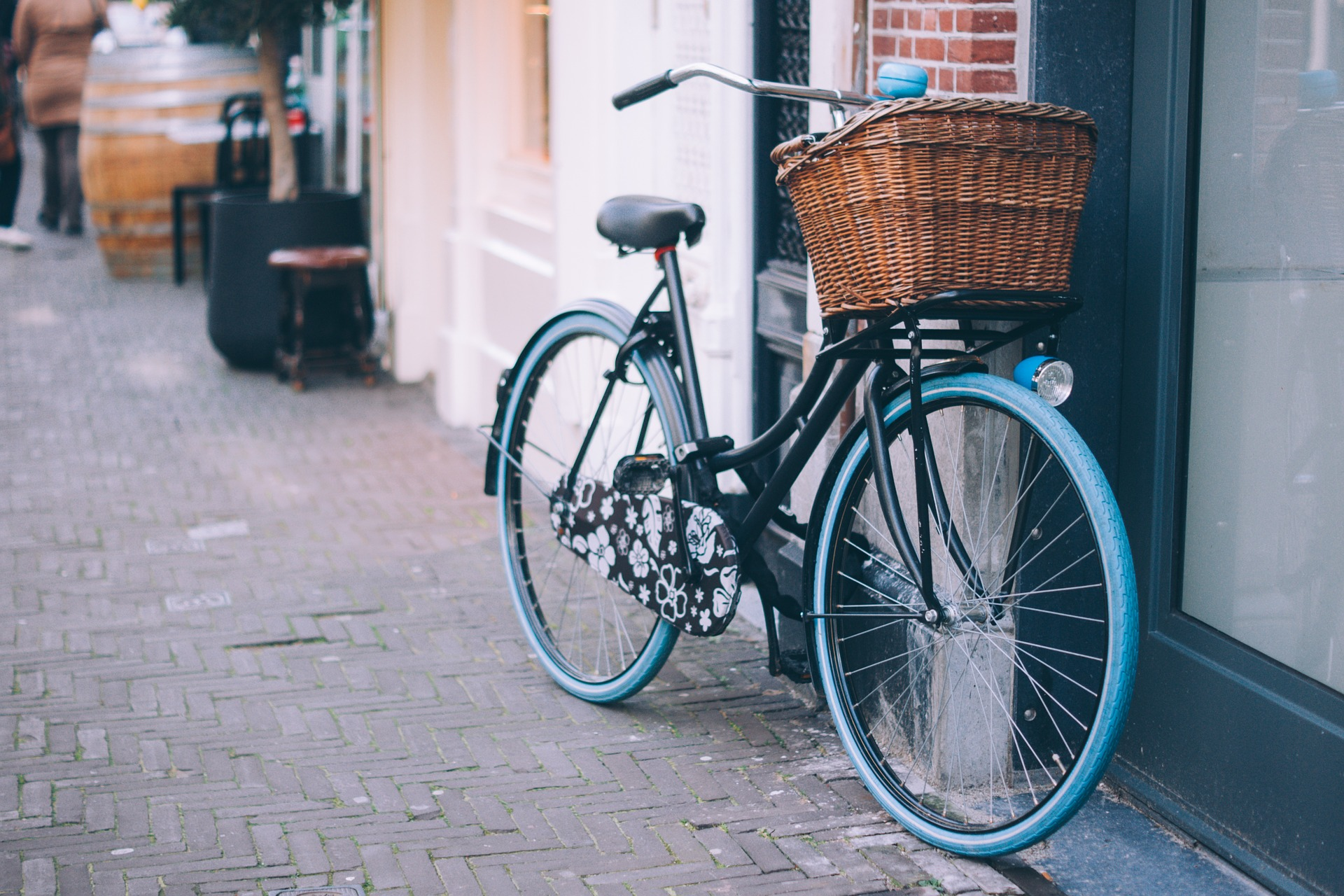 photo showing a bicycle with wicker pannier leaning against a wall in a street, cafe bar in the background