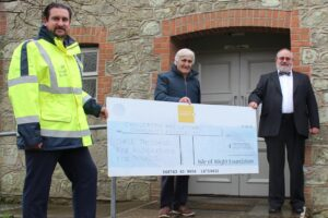 Photo showing Island Roads employee and members of Chillerton & Gatcombe community association holding a large cheque from the Isle of Wight Foundation