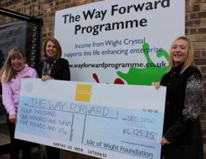 Photo showing Island Roads employee and members of The Way Forward programme holding a large cheque from the Isle of Wight Foundation