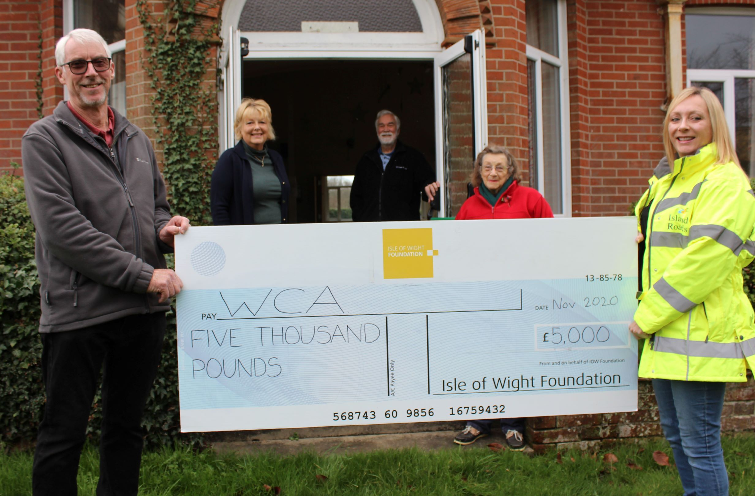 Photo showing Island Roads employee and members of the Whippingham Community Association holding a large cheque from the Isle of Wight Foundation
