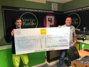Photo showing two people one from Island Roads and one from Vectis Radio in their studio holding a large cheque