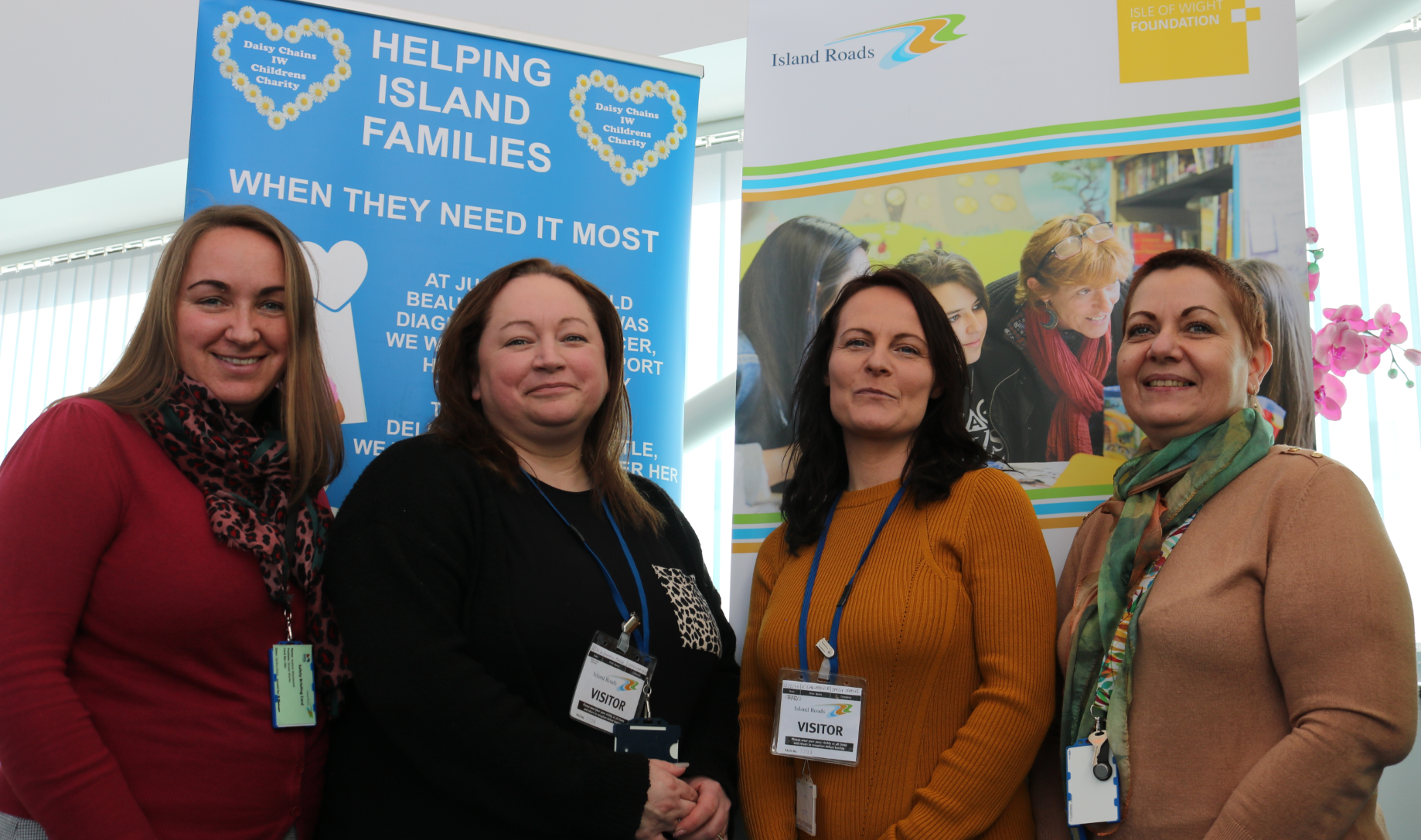 Photo showing four people, two from Daisy Chains charity, two from Island Roads, in front of colourful banners promoting the charity and the IW Foundation