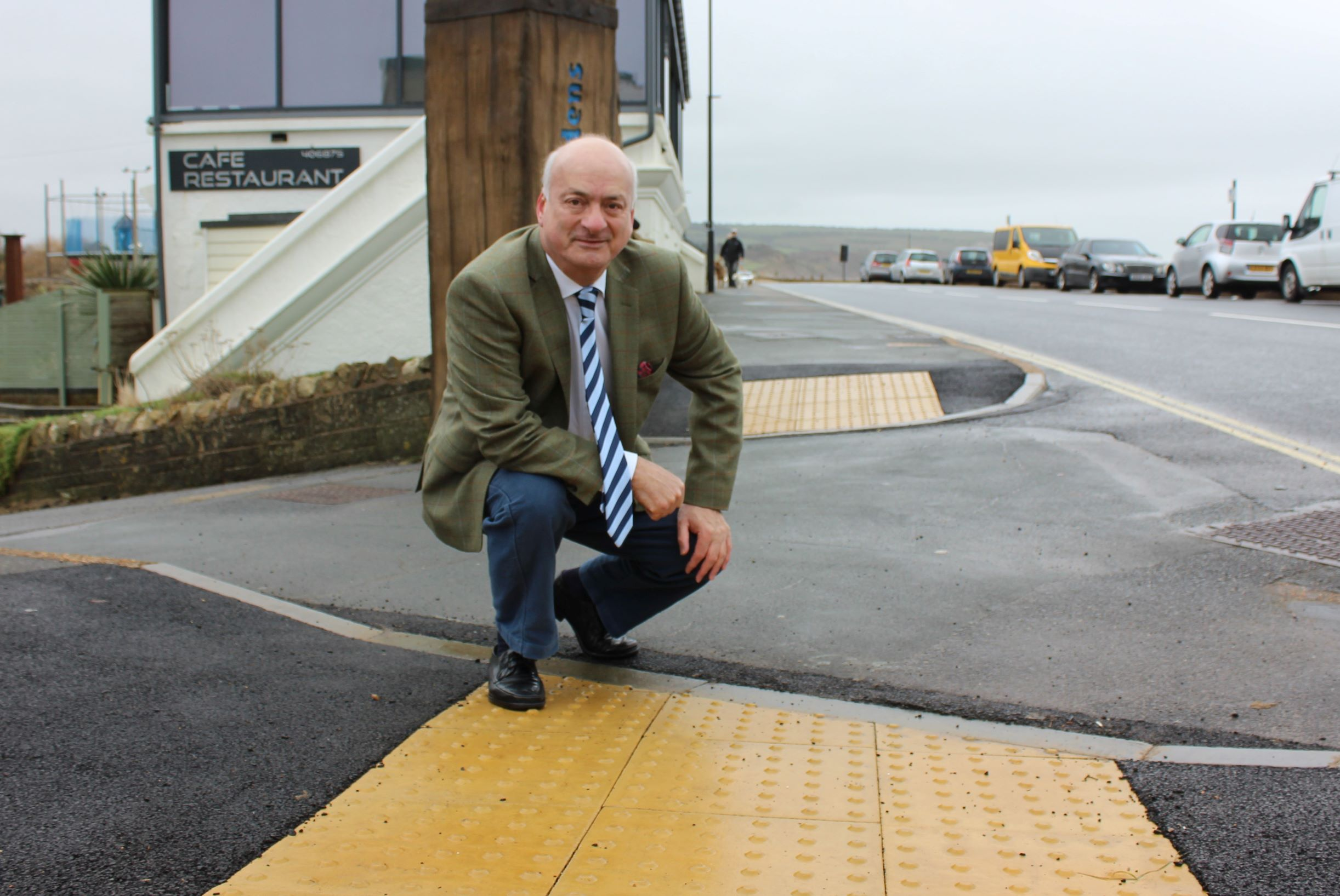 Photo shows a person (councillor Ian Ward) crouched down beside a tactile dropped kerb near the edge of the road