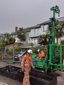 Photo shows two men operating a specialist engineering rig