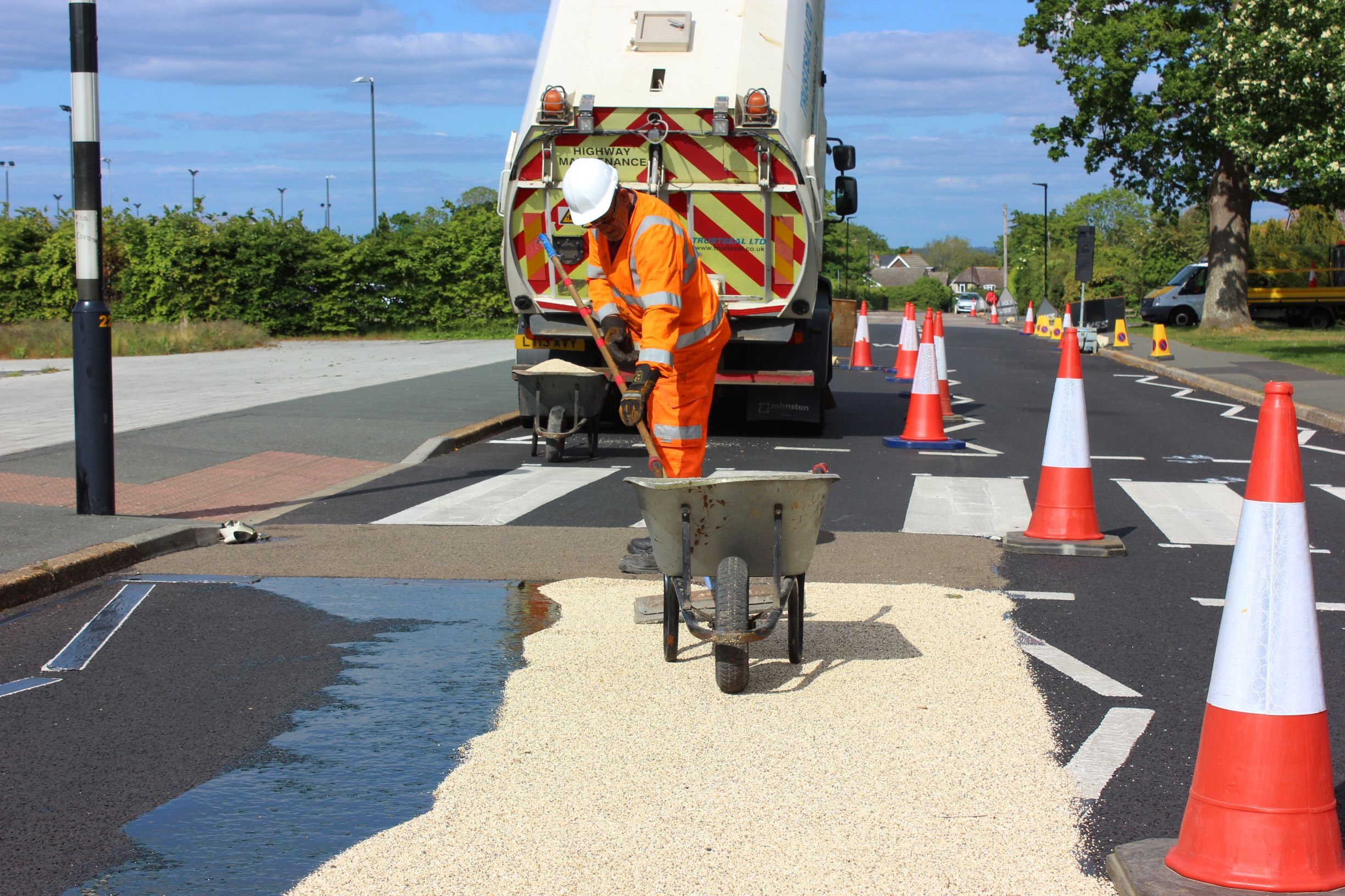 photo showing a workman and lorry laying high friction surfacing (a coarse material) in front of a pedestrian crossing