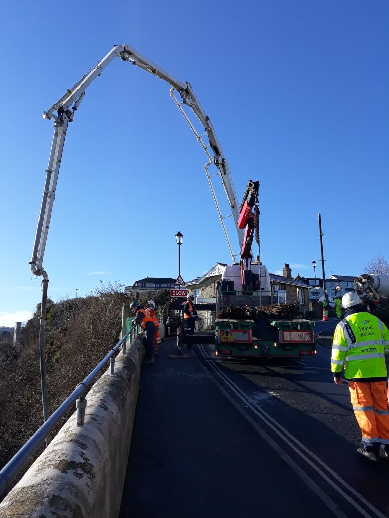 photo showing large crane reaching over wall, workmen in foreground