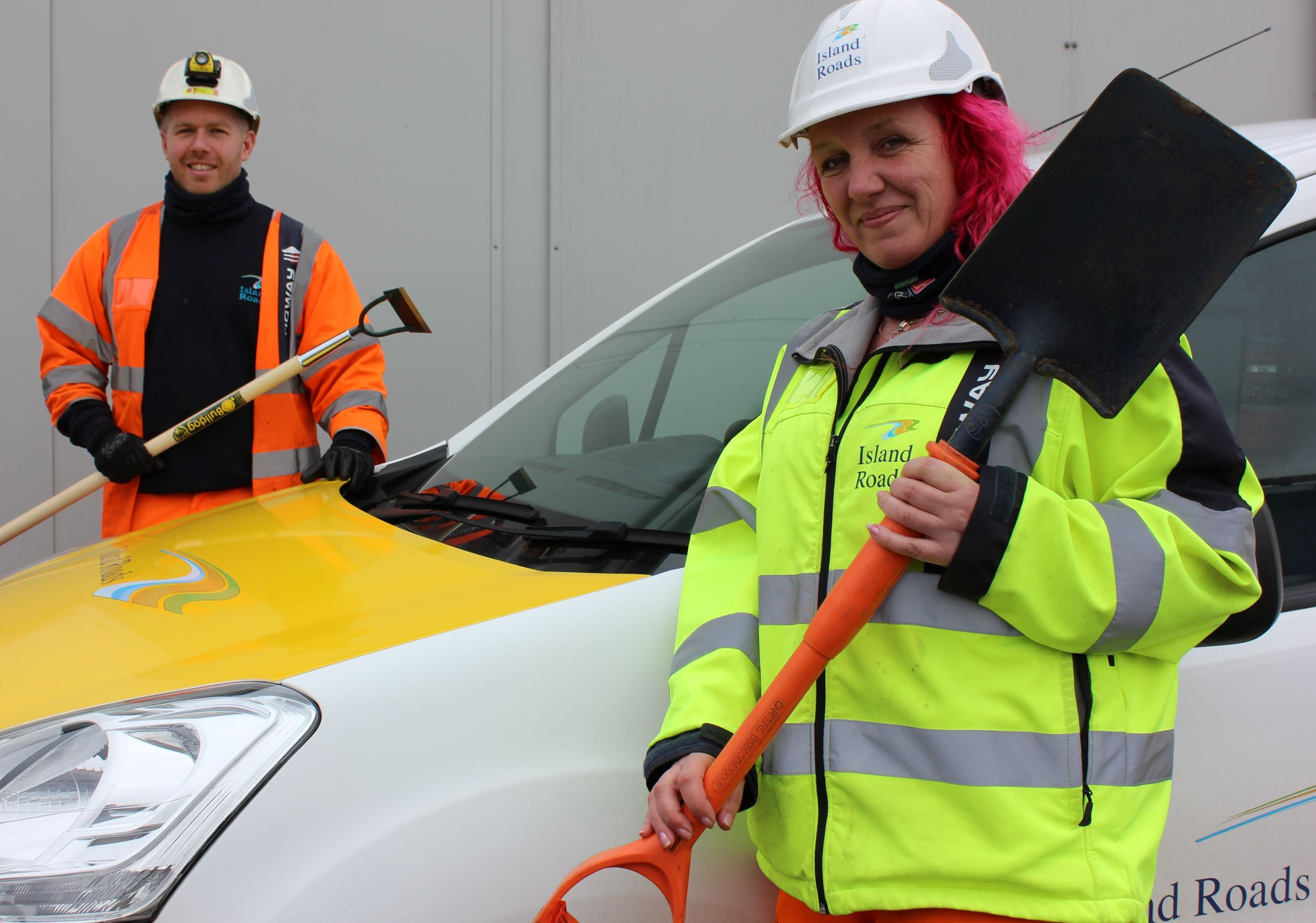 Photo showing two people one, a woman, in front of the vehicle holding a spade and one a man behind an Island Roads vehicle holding a hoe. Both are Island Roads staff, wearing branded clothing.