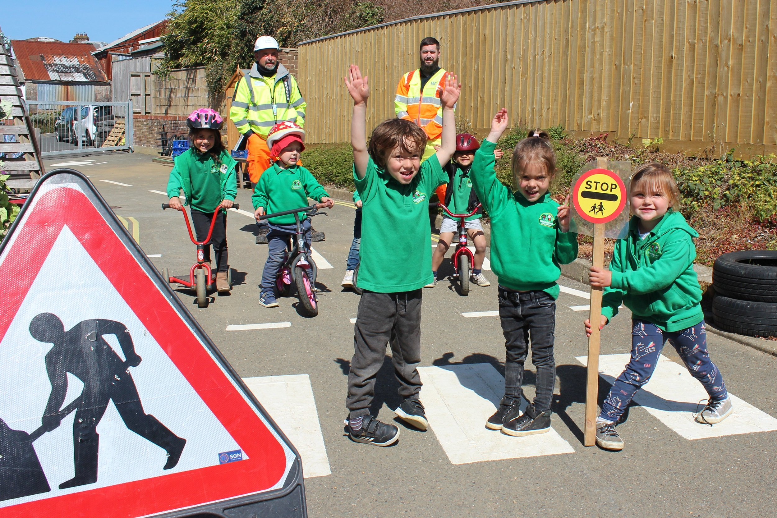 Photo showing school children on a pedestrian crossing that has been marked out on the playground, together with road signs, other children on bikes and Island Roads staff in the background