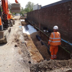Photo showing large dug out section of road, with pipes covered in highway materials, digger to the left and a workman standing in the pit in the foreground.