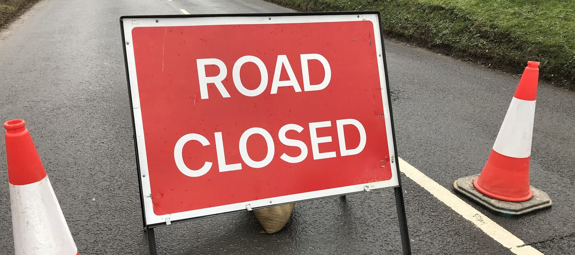 Photo showing road closed sign and traffic cones across a road with more signs and machinery in the background