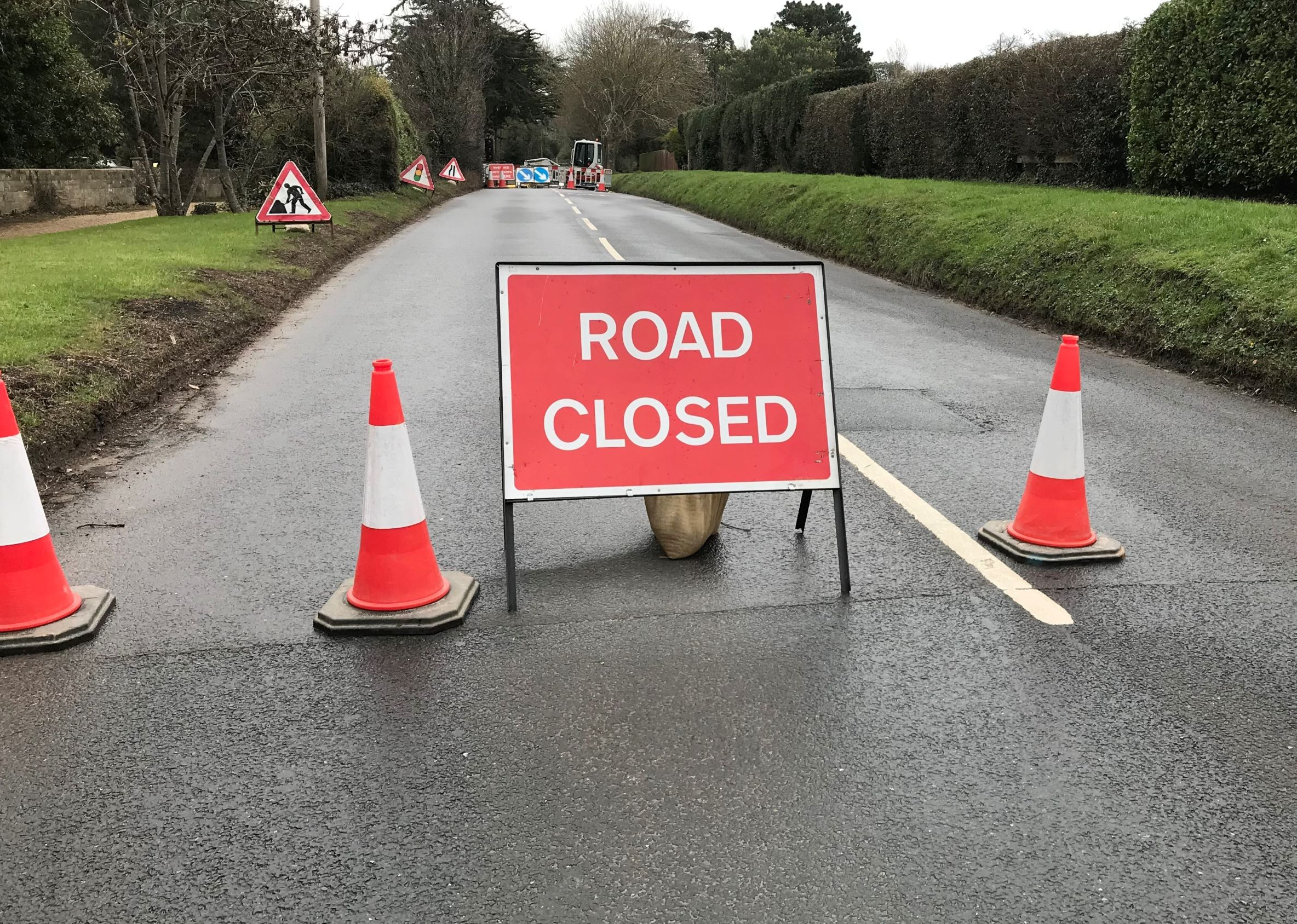 Photo showing road closed sign and traffic cones in the foreground and works equipment and machinery in the background in the middle of the road.