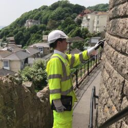 Photo showing a man in protective uniform (PPE) inspecting a wall with the town of Ventnor and seaside in the background