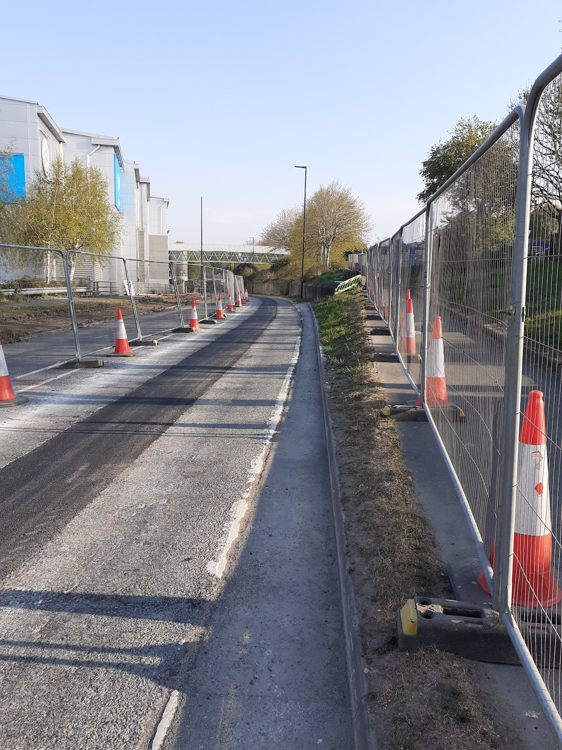 road with fencing on either side and traffic cones, surface of the road showing work underway
