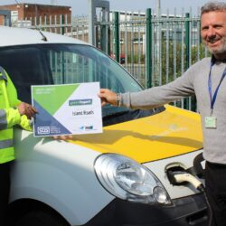 Nick Bhatnagar and Stephen Ambrose standing alongside an Island Roads electric vehicle holding the Green Impact gold award certificate