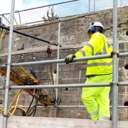 man in yellow hi visibility workwear standing on scaffolding adjacent to wall, other equipment visible in the background