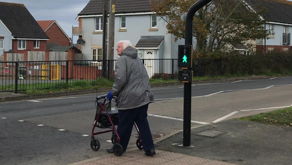 Older lady with walking aid crossing from tactile pavement at a pedestrian crossing housing estate in the background