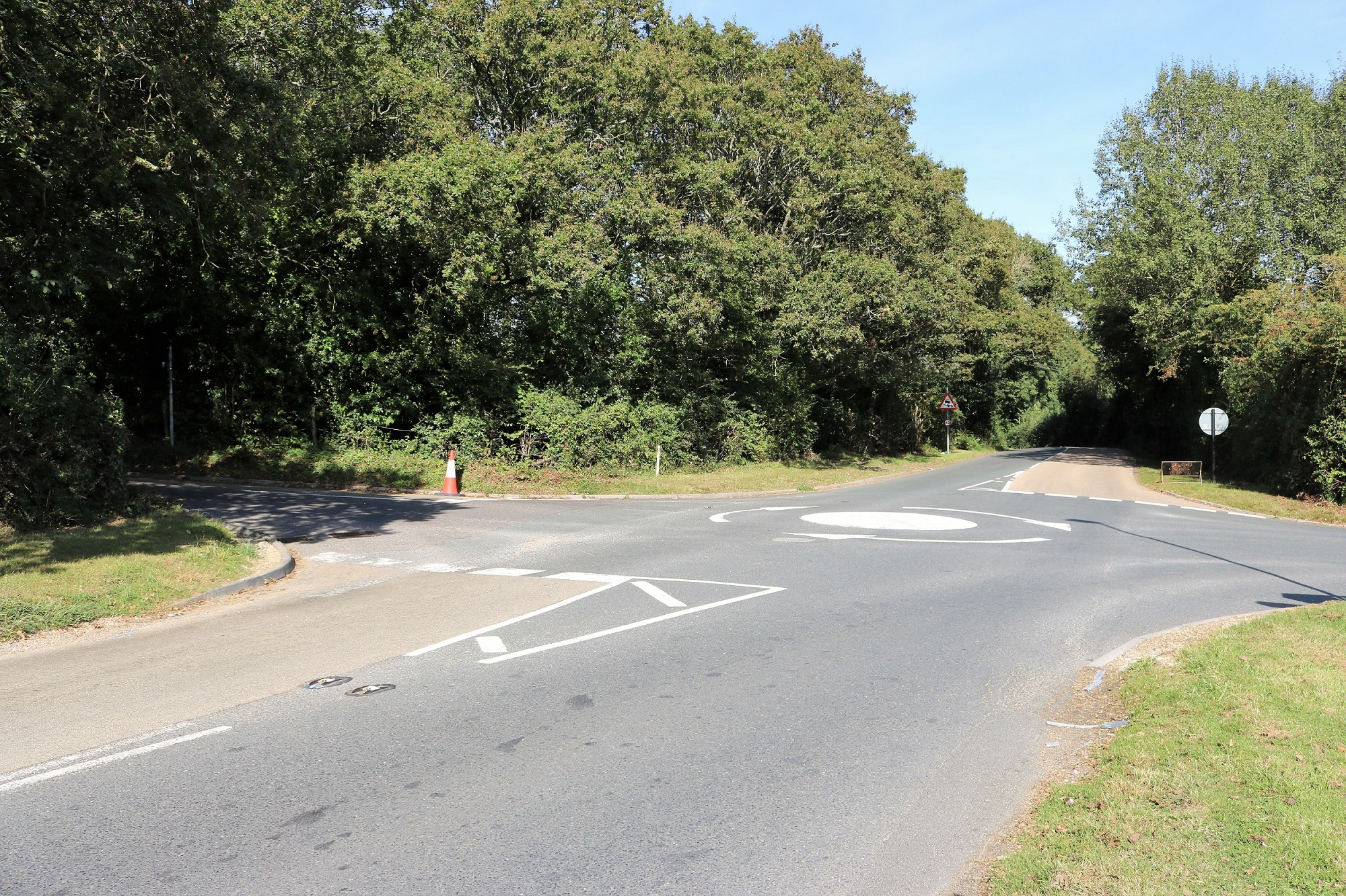 Four way road junction with mini roundabout, trees and hedging bordering the roadside